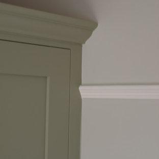 Imagen de dormitorio principal, tradicional, de tamaño medio, con paredes grises, suelo de madera en tonos medios, chimenea tradicional y marco de chimenea de metal