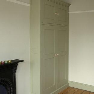 Imagen de dormitorio principal, clásico, de tamaño medio, con paredes grises, suelo de madera en tonos medios, chimenea tradicional y marco de chimenea de metal