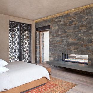 Idee per una camera matrimoniale contemporanea di medie dimensioni con pareti beige, parquet chiaro, camino bifacciale, cornice del camino in pietra e pavimento beige