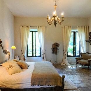 Immagine di una camera degli ospiti country di medie dimensioni con pareti multicolore, pavimento in pietra calcarea, camino classico e pavimento multicolore