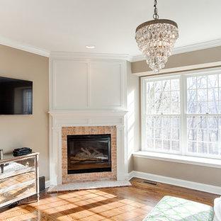Esempio di una camera matrimoniale chic di medie dimensioni con pareti beige, pavimento in legno massello medio, camino ad angolo, cornice del camino in mattoni e pavimento marrone