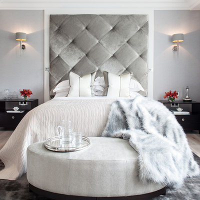 Example of a trendy master light wood floor bedroom design in London with gray walls and no fireplace