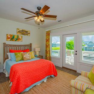 Foto de dormitorio costero con paredes verdes, suelo de madera oscura y suelo marrón