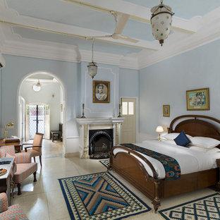Foto de dormitorio tradicional renovado, de tamaño medio, con paredes azules, suelo de cemento, chimenea tradicional y suelo blanco