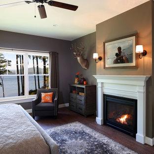 Cette photo montre une très grand chambre parentale chic avec un mur marron, un sol en bois foncé, une cheminée standard et un manteau de cheminée en bois.