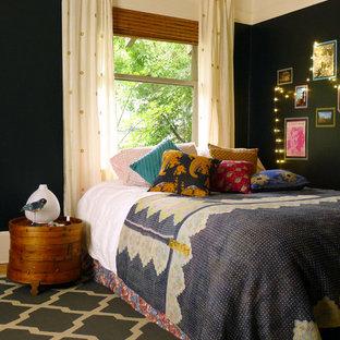 Esempio di una camera da letto bohémian con pareti nere e pavimento in legno massello medio