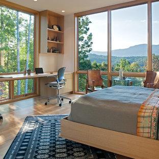 Diseño de dormitorio minimalista con paredes beige, suelo de madera clara y suelo beige