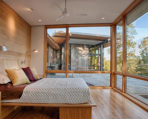 minimalist master medium tone wood floor and beige floor bedroom photo in charlotte with beige walls