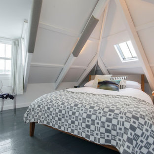 Photo of a small coastal bedroom in Cornwall with white walls, painted wood flooring, black floors and a vaulted ceiling.