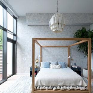 Esempio di una camera matrimoniale minimal con pareti multicolore e parquet chiaro