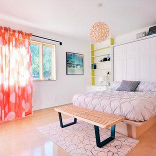 Foto di una camera da letto contemporanea con pavimento in compensato e pareti bianche
