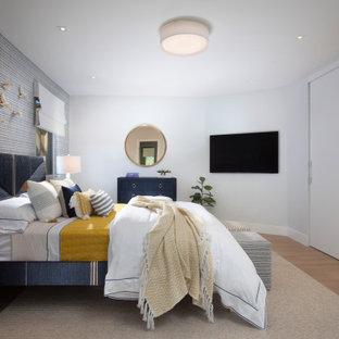 マイアミの広いビーチスタイルのおしゃれな客用寝室 (グレーの壁、暖炉なし、無垢フローリング、茶色い床、壁紙)