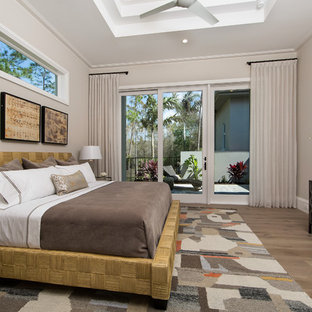 Transitional medium tone wood floor and brown floor bedroom photo in Miami with gray walls