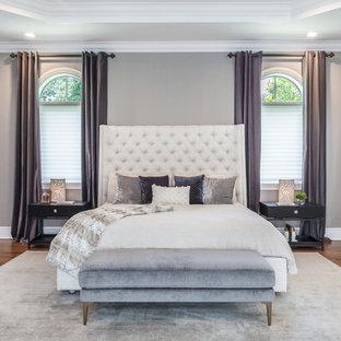 Immagine di una grande camera matrimoniale design con pareti grigie, pavimento in laminato, nessun camino e pavimento giallo