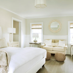 Inspiration for a beach style master medium tone wood floor bedroom remodel in Boston with beige walls