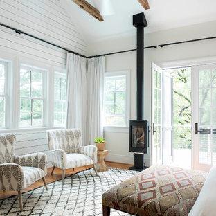 Modelo de dormitorio principal, tradicional, grande, con paredes beige, suelo de madera en tonos medios, estufa de leña, marco de chimenea de metal y suelo marrón