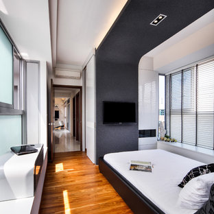Design ideas for a contemporary guest bedroom in Singapore with white walls and medium hardwood flooring.