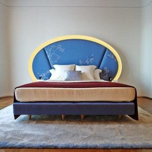 Idées déco pour une chambre éclectique avec un mur blanc et un sol en bois brun.