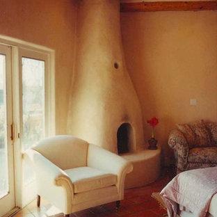 Неиссякаемый источник вдохновения для домашнего уюта: большая хозяйская спальня в стиле фьюжн с бежевыми стенами, полом из терракотовой плитки, угловым камином и фасадом камина из штукатурки