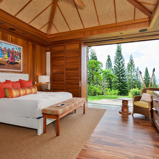 This is an example of a mid-sized tropical guest bedroom in Hawaii with brown floor, brown walls and medium hardwood floors.
