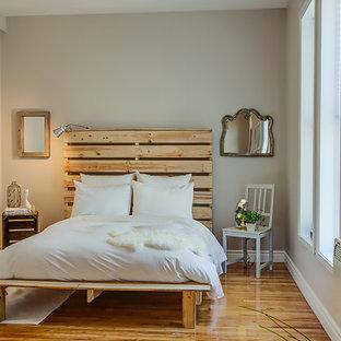 Imagen de dormitorio ecléctico, pequeño, sin chimenea, con paredes grises y suelo de madera en tonos medios