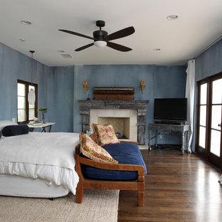 Modelo de dormitorio principal, rural, extra grande, con paredes azules, suelo de madera oscura, chimenea tradicional, marco de chimenea de piedra y suelo marrón