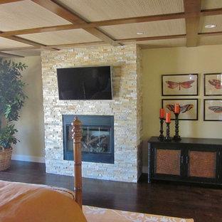 Modelo de dormitorio principal, tropical, grande, con paredes beige, suelo de madera oscura, chimenea tradicional, marco de chimenea de piedra y suelo marrón