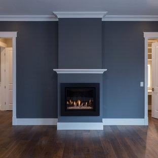 サンフランシスコの大きいトラディショナルスタイルのおしゃれな主寝室 (グレーの壁、濃色無垢フローリング、標準型暖炉、漆喰の暖炉まわり、茶色い床) のレイアウト