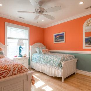 Ejemplo de habitación de invitados costera, de tamaño medio, sin chimenea, con parades naranjas, suelo de madera clara y suelo marrón