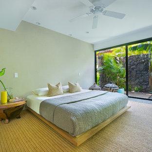 Ispirazione per una grande camera degli ospiti tropicale con pareti grigie, pavimento in cemento e pavimento beige