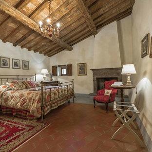 Ejemplo de dormitorio principal, de estilo de casa de campo, grande, con paredes blancas, suelo de baldosas de terracota, chimenea tradicional y marco de chimenea de piedra