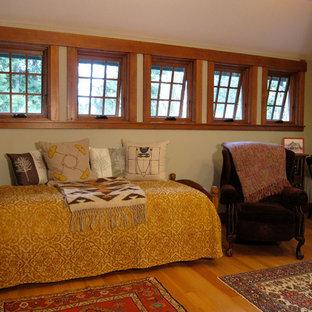 Imagen de dormitorio tipo loft, de estilo americano, de tamaño medio, sin chimenea, con paredes verdes, suelo de madera en tonos medios y suelo marrón