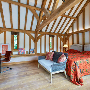 Photo of a large rustic guest bedroom in Berkshire with white walls, medium hardwood flooring and beige floors.