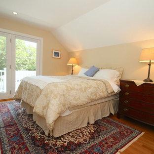 Ejemplo de dormitorio principal, tradicional, grande, sin chimenea, con paredes amarillas, suelo de madera en tonos medios y suelo marrón