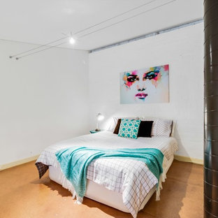 Design ideas for a mid-sized industrial loft-style bedroom in Adelaide with white walls and cork floors.
