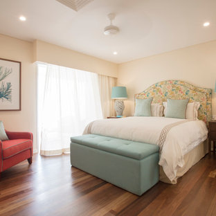 Inspiration for a beach style bedroom in Cairns with yellow walls, dark hardwood floors and no fireplace.