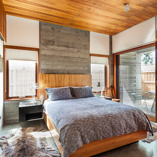 This is an example of a country master bedroom in Melbourne with white walls and concrete floors.
