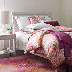 Portico Duvet Cover - Intricate medallions recalling fine ironwork and stained glass windows feel airy and modern in shades of wine, berry, purple and orange floating across the palest pink ground. The duvet cover and shams are trimmed with berry-hued velvet for an elegant finishing touch. Printed on 100% cotton percale. Shown with the Portico Rug and Madeline Fuchsia Sheet Set. Photo by Company C.