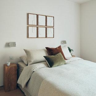 Foto de dormitorio principal, actual, de tamaño medio, con paredes blancas, suelo de madera clara y suelo beige