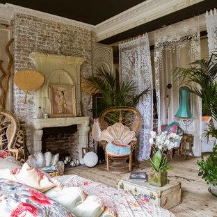 Immagine di una camera matrimoniale stile shabby con parquet chiaro, camino classico e cornice del camino in mattoni