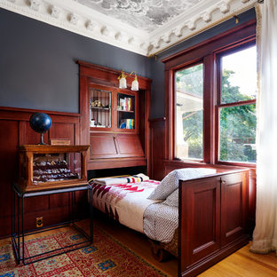 Example of a mid-sized eclectic guest medium tone wood floor bedroom design in Portland with black walls