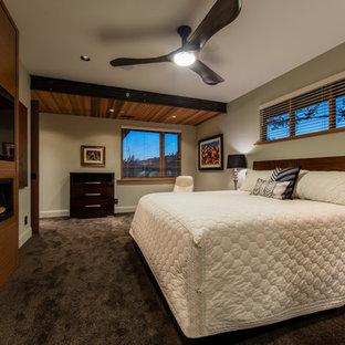 Idéer för att renovera ett stort amerikanskt huvudsovrum, med heltäckningsmatta, bruna väggar, brunt golv, en bred öppen spis och en spiselkrans i trä