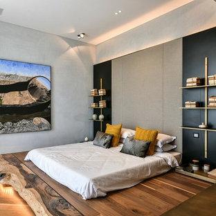 Diseño de dormitorio contemporáneo, de tamaño medio, con paredes grises, suelo de madera en tonos medios y suelo marrón