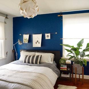 Ejemplo de dormitorio principal, retro, de tamaño medio, sin chimenea, con paredes azules y suelo de madera clara