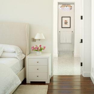 Mediterranes Schlafzimmer mit weißer Wandfarbe, braunem Holzboden und braunem Boden in San Diego