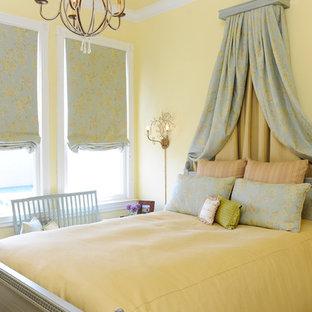 Foto di una camera da letto chic con pareti gialle