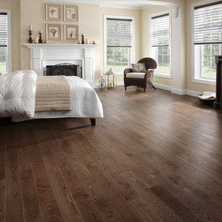 Ejemplo de dormitorio principal, clásico renovado, con paredes beige, suelo de madera oscura, chimenea tradicional y marco de chimenea de madera
