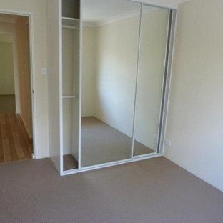 Esempio di una piccola camera degli ospiti moderna con pareti bianche e moquette