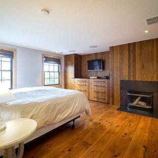 Ejemplo de dormitorio principal, rural, de tamaño medio, con paredes blancas, suelo de mármol, suelo blanco, chimenea tradicional y marco de chimenea de metal