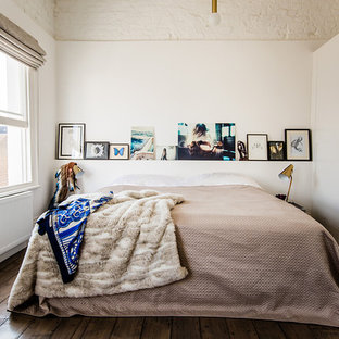 Esempio di una camera da letto boho chic con pareti bianche e pavimento in legno massello medio